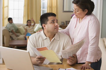 Hispanic couple paying bills online
