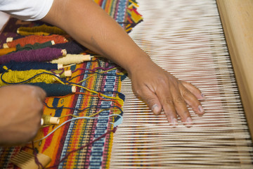 Close up of Hispanic man weaving textile