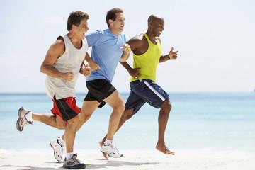 Multi-ethnic men running in beach