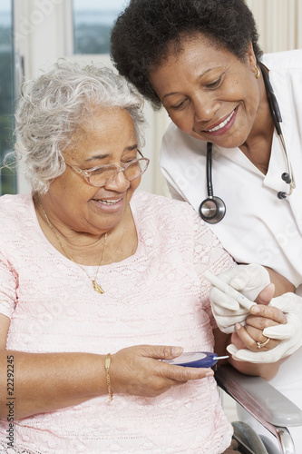 Doctor testing African American woman's blood sugar