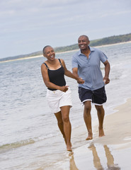 Senior African American couple running on beach