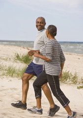Senior African American couple running at beach