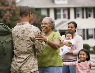 African American male soldier greeting family