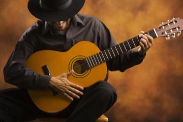Hispanic man playing acoustic guitar