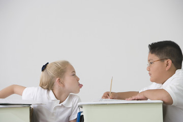 Girl sticking out tongue at boy in class