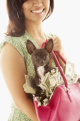 Asian woman holding handbag full of money and dog