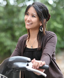 Verry pretty young asian woman on bike smiling while commuting/b poster