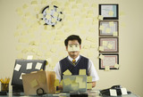 Asian businessman with sticky notes all over wall and face
