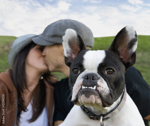 Multi-ethnic couple kissing behind dog