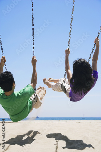 Asian couple swinging at beach