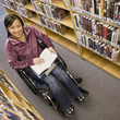 Asian woman in wheelchair at library