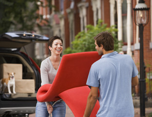 Hispanic couple carrying furniture