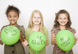 Multi-ethnic girls holding green balloons