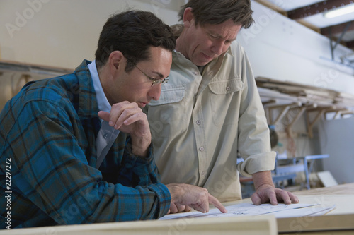 Multi-ethnic men looking paperwork in wood shop