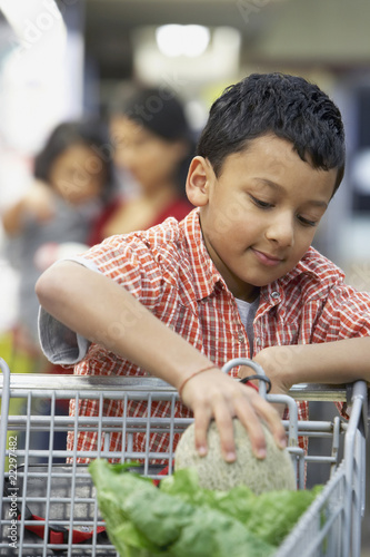 Indian boy putting fruit in shopping cart