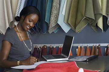 African businesswoman writing on calendar
