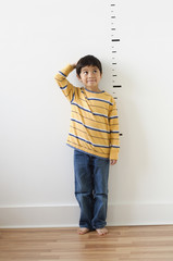 Asian boy standing next to height markers on wall