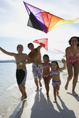 Hispanic family flying kite at beach