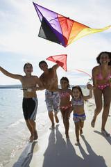 Hispanic family flying kite at beach