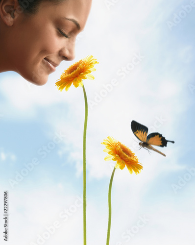 Hispanic woman smelling flower