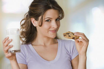 Woman holding chocolate chip cookie and milk