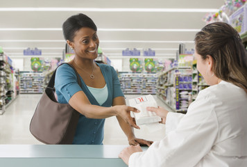 African woman picking up prescription at pharmacy