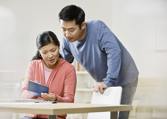 Asian couple looking at checkbook