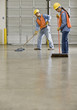 Multi-ethnic warehouse workers sweeping floor