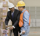 Multi-ethnic businessman and warehouse worker talking