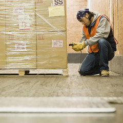 Asian warehouse worker scanning shipment