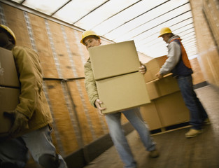 Multi-ethnic warehouse workers carrying boxes