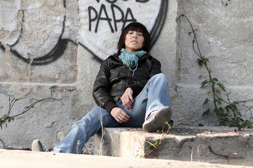 Urban Attitude.  Woman sitting against the wall with graffiti