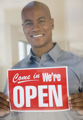African man holding Open sign