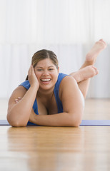 Overweight Hispanic woman laying on yoga mat
