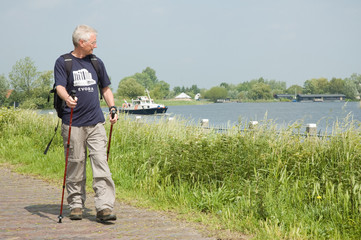 Senior man doing a Nordic Walk on a sunny day.
