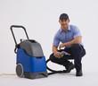 Hispanic man holding vacuum hose