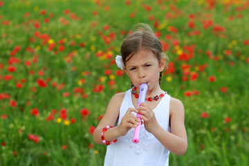 Pretty young girl playing the recorder in a poppy field