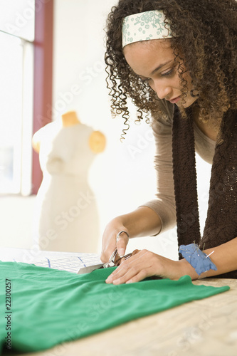 African woman cutting fabric on pattern