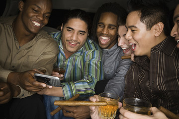 Multi-ethnic men celebrating in limousine