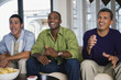 Multi-ethnic men sitting on sofa