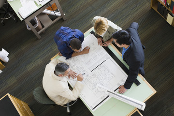 Multi-ethnic architects looking at blueprints