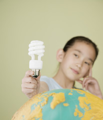 Asian girl holding light bulb over globe