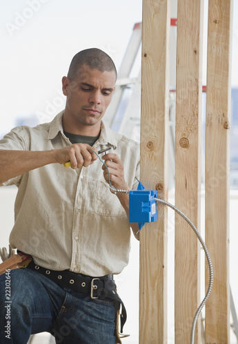 Hispanic male electrician working in new construction