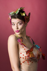 Concept of spring. Sexy woman with butterflies in studio