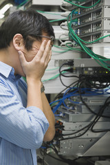 Frustrated Asian man in computer server room