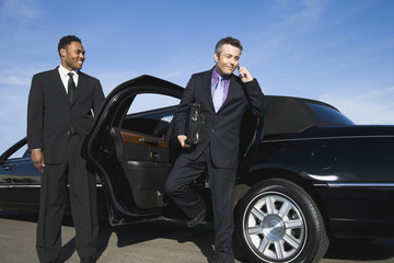 Hispanic businessman getting out of limousine