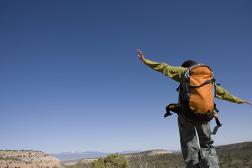 African woman with arms outstretched hiking in wilderness