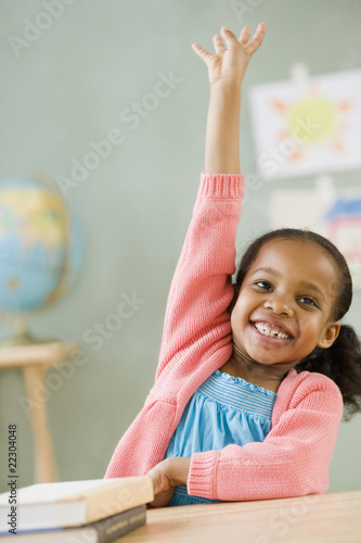 Mixed race girl raising hand to answer question