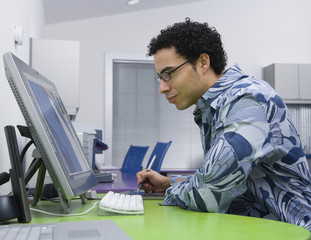 African graphic designer working on computer in office
