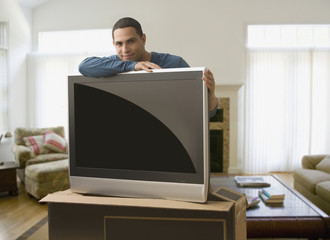 Hispanic man leaning on new television